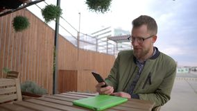 Adult man is resting in open terrace of cafe, calling by video in smartphone stock footage