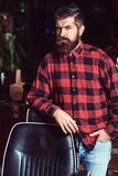 Handsome bearded hipster male at barbershop. Barber man at work. Stylish man with beard in plaid shirt standing near vintage stock images