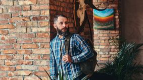 Handsome bearded hipster male in a blue fleece shirt and jeans with backpack leaning against a brick wall at a studio royalty free stock photo