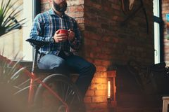 Handsome bearded hipster male in a blue fleece shirt and jeans holds a cup of morning coffee while sitting on a window royalty free stock image