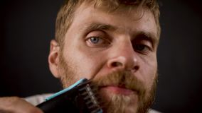 Handsome bearded hipster male shaves in the black dark room.  stock video
