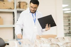 Quality Control Inspector at Work. Handsome bearded inspector wearing lab coat holding clipboard in hands while conducting quality control at warehouse of Royalty Free Stock Photo
