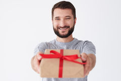 Handsome bearded male in cheerful mood holding gift and smiling Royalty Free Stock Photography