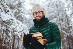 Handsome bearded male in eyewear and warm hat with anorak, holds firewood, poses against trees covered with white sparkling snow,. Spends time in forest royalty free stock image