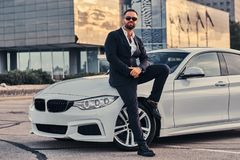 Handsome bearded male in sunglasses dressed in a black suit sitting on luxury car against a skyscraper. Handsome bearded male in sunglasses dressed in a black Stock Photography