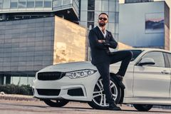 Handsome bearded male in sunglasses dressed in a black suit sitting on luxury car against a skyscraper. Handsome bearded male in sunglasses dressed in a black Royalty Free Stock Photography