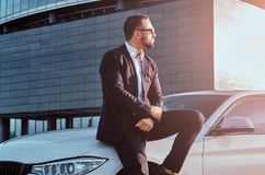 Handsome bearded male in sunglasses dressed in a black suit sitting on luxury car against a skyscraper. Handsome bearded male in sunglasses dressed in a black Royalty Free Stock Photo