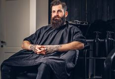 Handsome bearded man in the barbershop. Handsome bearded male with a tattoo on his arms before hair wash in a hairdressers salon royalty free stock photography