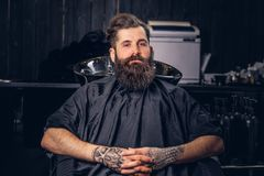 Handsome bearded man in the barbershop. Handsome bearded male with a tattoo on his arms before hair wash in a hairdressers salon royalty free stock photo