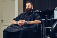 Handsome bearded man in the barbershop. Handsome bearded male with a tattoo on his arms before hair wash in a hairdressers salon royalty free stock images