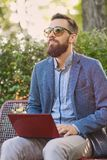 Handsome bearded male using laptop in a park. Close up image Royalty Free Stock Image