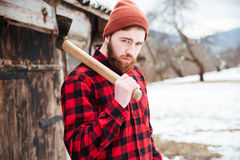 Handsome bearded man with axe in village Stock Image