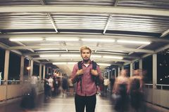 Handsome bearded man with backpack standing on the street travel. Ing at night background stock photography