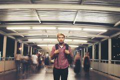 Handsome bearded man with backpack standing on the street travel. Ing at night background stock photo