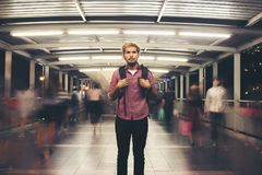 Handsome bearded man with backpack standing on the street travel. Ing at night background stock images