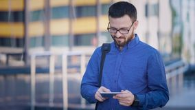 Handsome bearded man with bag across his shoulder in blue shirt and brown trousers is standing typing messages using his stock video