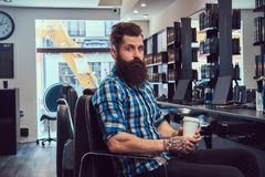 Handsome bearded man in the barbershop. A handsome stylish bearded male with a tattoo on arm dressed in a flannel shirt drinks coffee in a barbershop stock photo