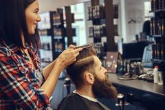 Handsome bearded man in the barbershop. Professional hairdresser making hairstyle with a comb in a barbershop royalty free stock images