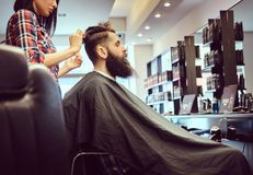 Handsome bearded man in the barbershop. Professional hairdresser making hairstyle with a comb in a barbershop royalty free stock image