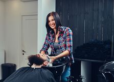 Handsome bearded man in the barbershop. Professional hairdresser washing clients hair in a barbershop royalty free stock photo