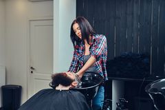 Handsome bearded man in the barbershop. Professional hairdresser washing clients hair in a barbershop stock photo