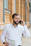 Handsome bearded man chatting on his mobile Stock Images