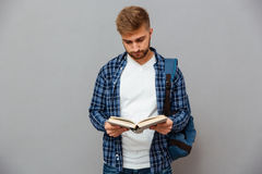 Handsome bearded man in checkered shirt with backpack reading book Stock Photo