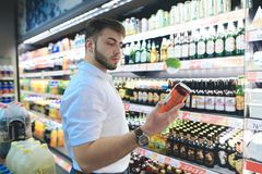 A handsome bearded man chooses beer in a supermarket. The buyer buys alcohol at a supermarket. A man looks at a can of beer stock photography