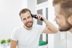 Handsome man cutting his own hair with a clipper stock photos