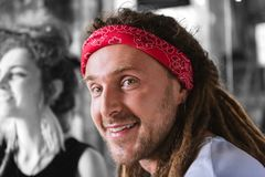 Handsome bearded man with dreadlocks wearing red head band smiling broadly