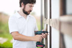 Handsome bearded man drilling wooden house wall. Portrait of man working with electric drill. DIY repair outdoors Stock Images