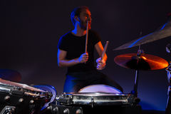 Handsome bearded man drummer sitting and plaing on drums Stock Photos