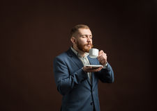 Handsome bearded man enjoying smell of coffee Stock Image