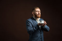 Handsome bearded man enjoying smell of coffee Royalty Free Stock Photos