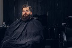 Handsome bearded man in the barbershop. Handsome bearded man with before hair wash in a hairdressers salon royalty free stock photo
