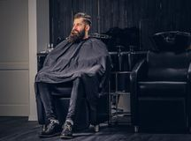 Handsome bearded man in the barbershop. Handsome bearded man with before hair wash in a hairdressers salon stock images