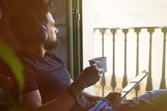 Handsome bearded man in headphones listening to music on electronic tablet and drinking coffee at home. Casual relaxing Royalty Free Stock Photo