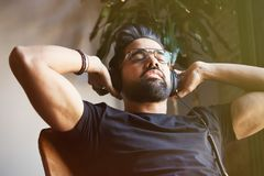 Handsome bearded man in headphones listening to music at home. Relaxing and rest time concept. Blurred background