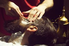 Bearded man has shave. Handsome bearded man, hipster, brunette with beard and moustache has shave in barbershop. Barber works with vintage razor and shaving foam royalty free stock images