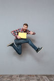 Handsome bearded man holding copyspace blank jumping. Picture of handsome bearded man holding copyspace blank jumping over grey background and pointing Royalty Free Stock Photography