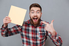Handsome bearded man holding copyspace blank. Photo of handsome bearded man holding copyspace blank standing over grey background and pointing Stock Photography