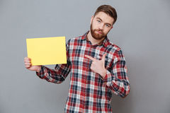 Handsome bearded man holding copyspace blank. Picture of handsome bearded man holding copyspace blank standing over grey background and pointing Royalty Free Stock Photography