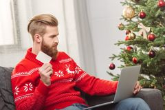 Man shopping online at christmas. Handsome bearded man holding credit card and using laptop while shopping online at christmas Stock Images