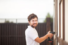 Handsome bearded man holding electric drill, copyspace Royalty Free Stock Images