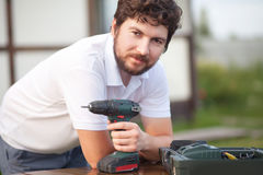 Handsome bearded man holding electric drill. Portrait of man holding drill machine, ready to work. DIY repair Stock Image
