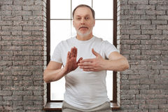 Handsome bearded man holding hands in yoga position Royalty Free Stock Photos