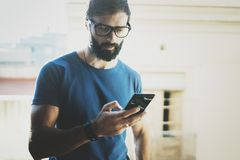 Handsome bearded man holding smartphone hands and touching screen of modern mobile phone. Blurred background.Blogger Stock Photography