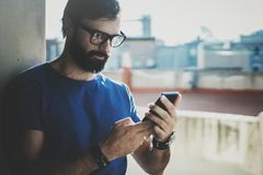 Handsome bearded man holding smartphone hands and touching screen of modern mobile phone. Blurred background.Blogger Stock Image