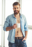 Handsome bearded man at home. Handsome bearded man in unbuttoned shirt is holding a cup, looking at camera and smiling while standing near the window at home Stock Image