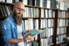 Free Handsome Bearded Man In Glasses Reading Book In Library Royalty Free Stock Image - 124580056